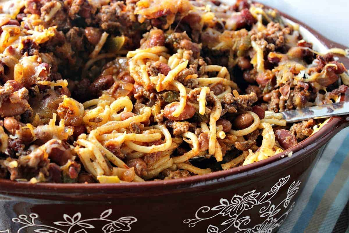 An oval brown casserole dish filled with spaghetti western casserole with ground beef and pasta