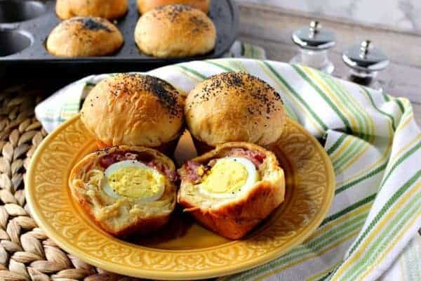 Hard boiled eggs wrapped in a biscuit with ham and cheese on a golden color plate with a muffin tin in the background.
