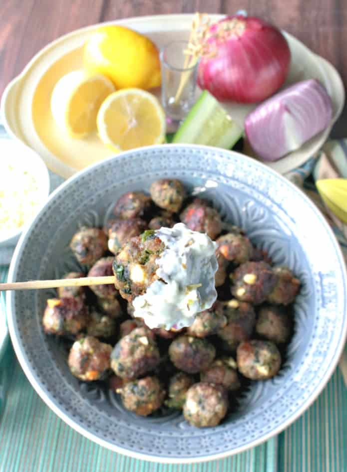 Closeup of a Greek meatball appetizer on a toothpick with tzatziki sauce. New Year's eve appetizers and drinks recipe roundup.