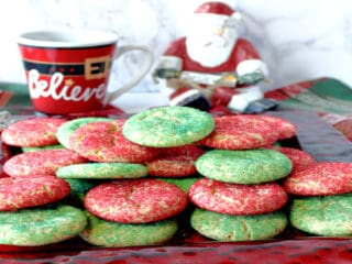 A red glass plate filled with Santa's Favorite Sugar Cookies in red and green along with a coffee mug in the background.