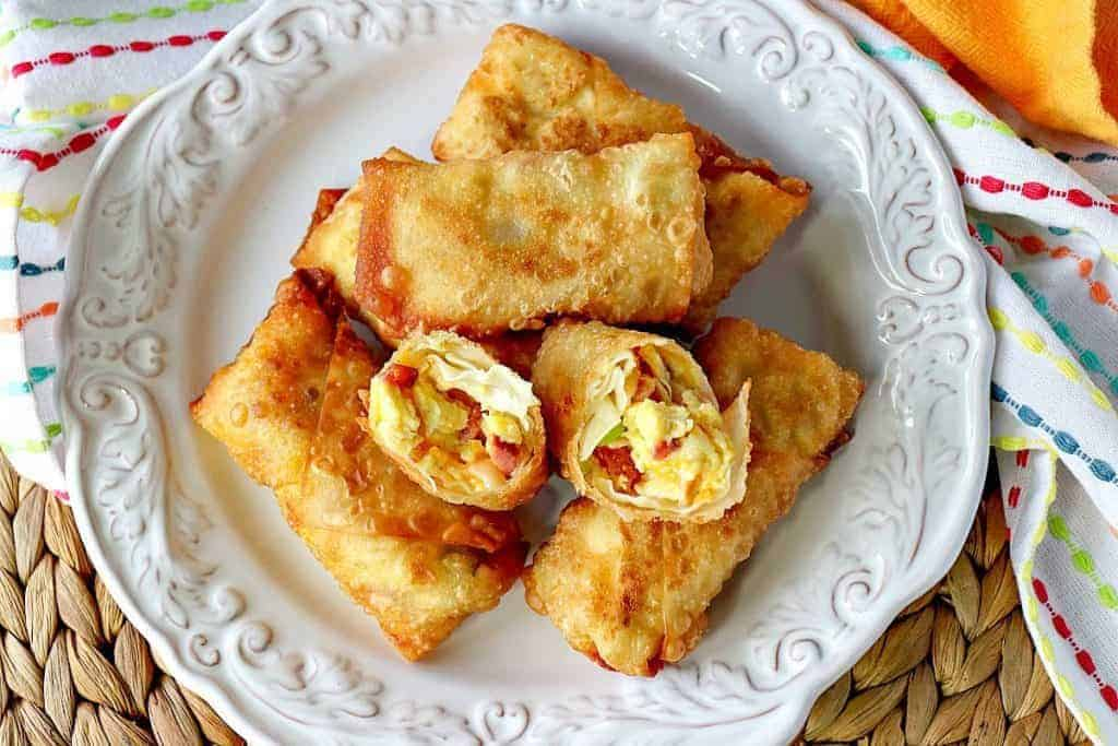 Overhead picture of scrambled egg rolls on a white plate with a bright yellow napkin.