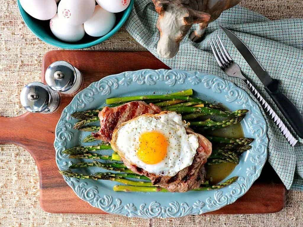 Overhead picture of steak, egg, and asparagus on a blue oval plate with a bowl of eggs in the background.