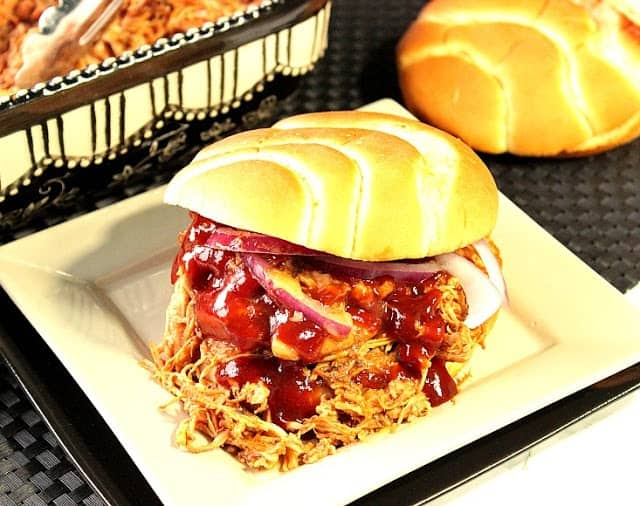 A horizontal photo of an easy family dinner of slow-cooker bbq pulled chicken sandwich on a square white plate with sauce and onions.