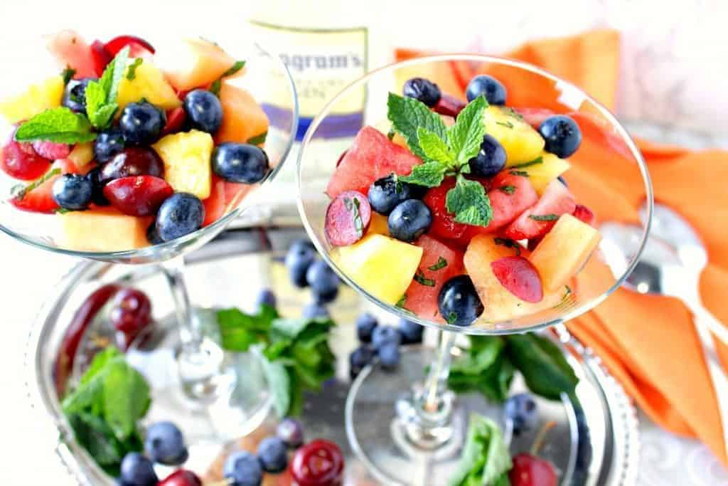 Overhead photo of two martini glasses filled with colorful fruit salad and mint.