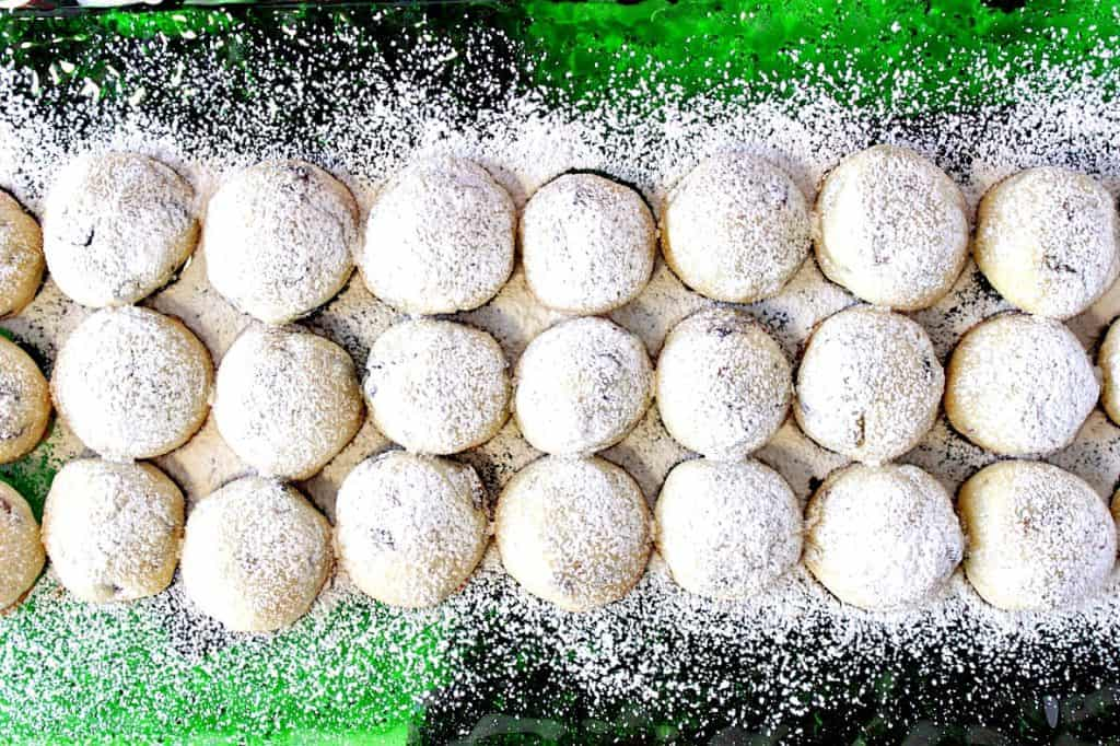 An overhead photo of a green glass plate filled with holiday snowball cookies dusted with confectioners sugar.