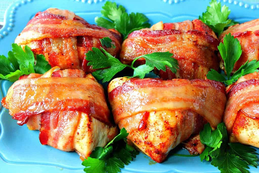 Smoky Sweet Bacon Wrapped Chicken Breasts on a blue plate with parsley as garnish.