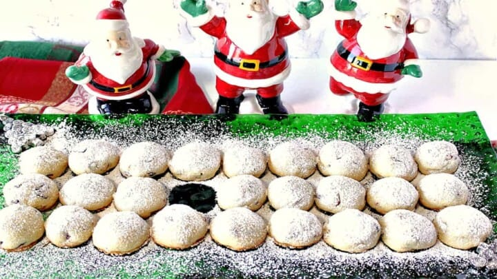 A horizontal image of snowball cookies on a green glass holiday plate dusted with confectioners sugar with one cookie missing.