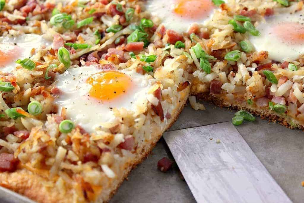 Closeup photo of a hash brown breakfast pizza with a slice taken out and over easy eggs on top.