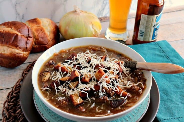 A bowl of German onion soup with onions and pretzel roll in the background along with a glass of beer.
