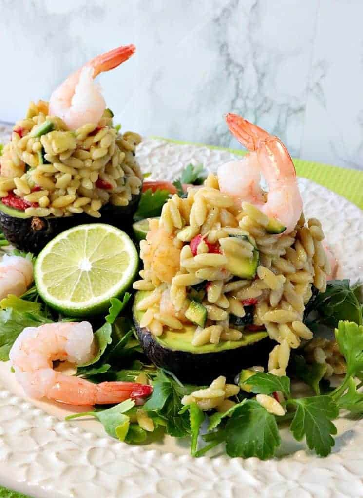 A vertical photo of two elegant avocados stuffed with vegetable orzo pasta salad, with shrimp and limes.