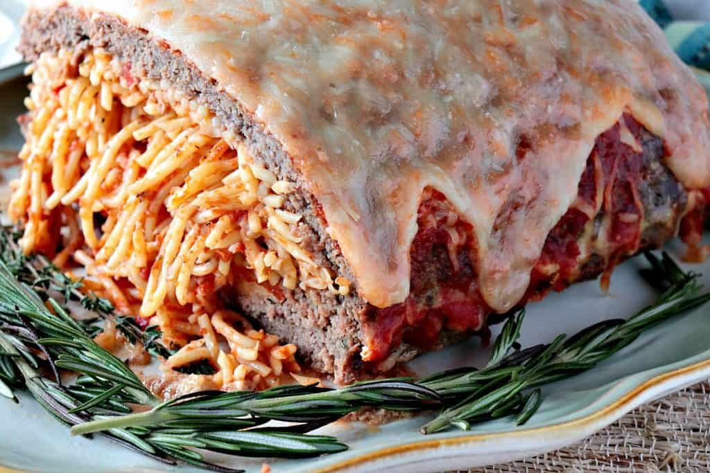 A meatloaf filled with spaghetti and topped with tomato sauce and cheese.