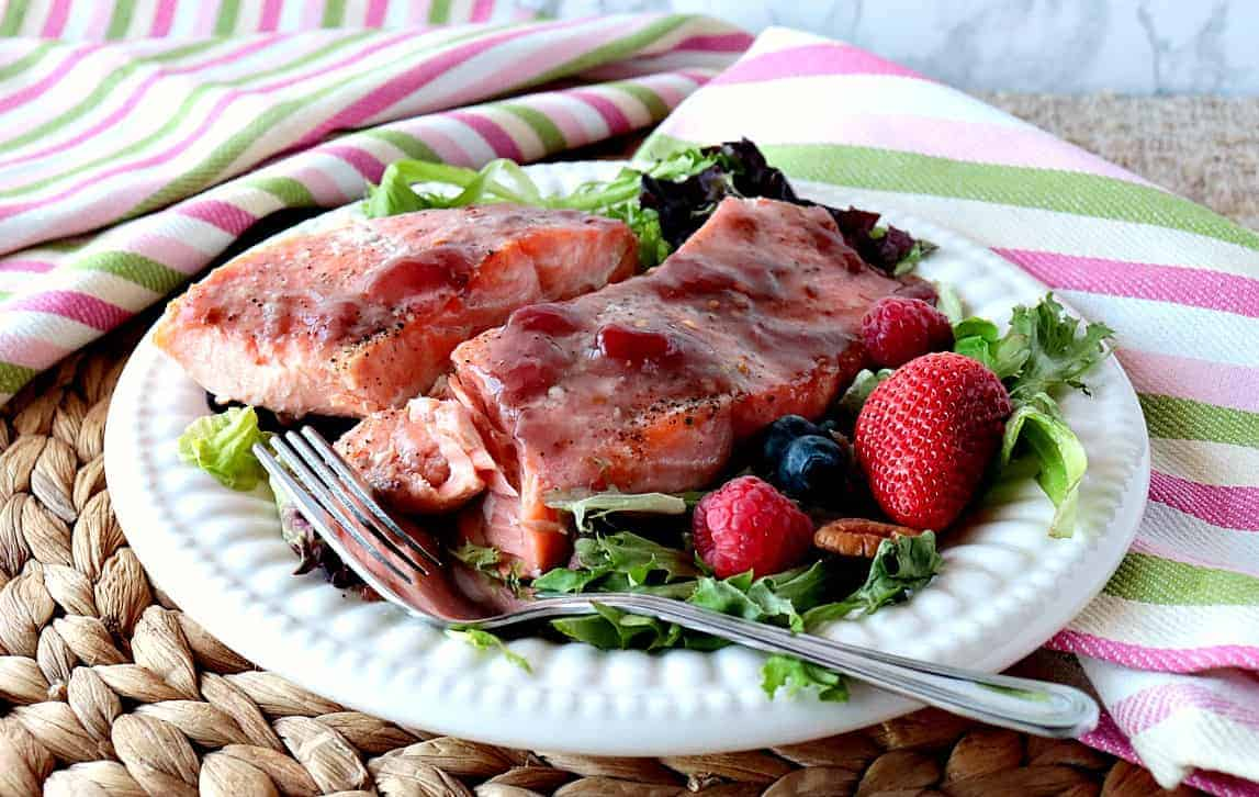 Strawberry Glazed Salmon fillets on a white plate with greens and berries.