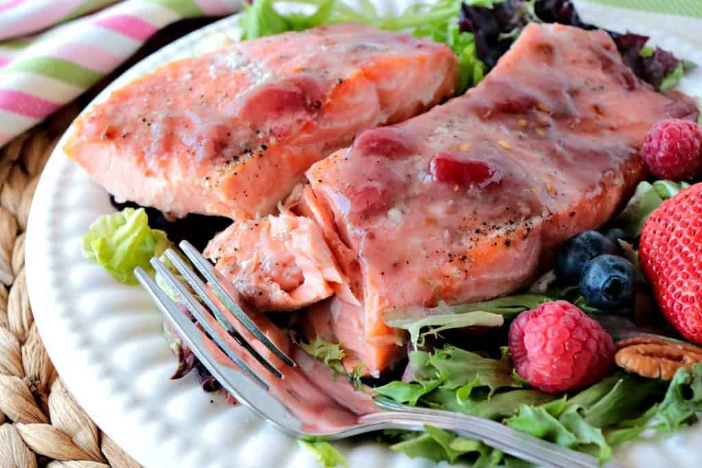 Flaky salmon fillets on a white plate with a fork, berries and greens.