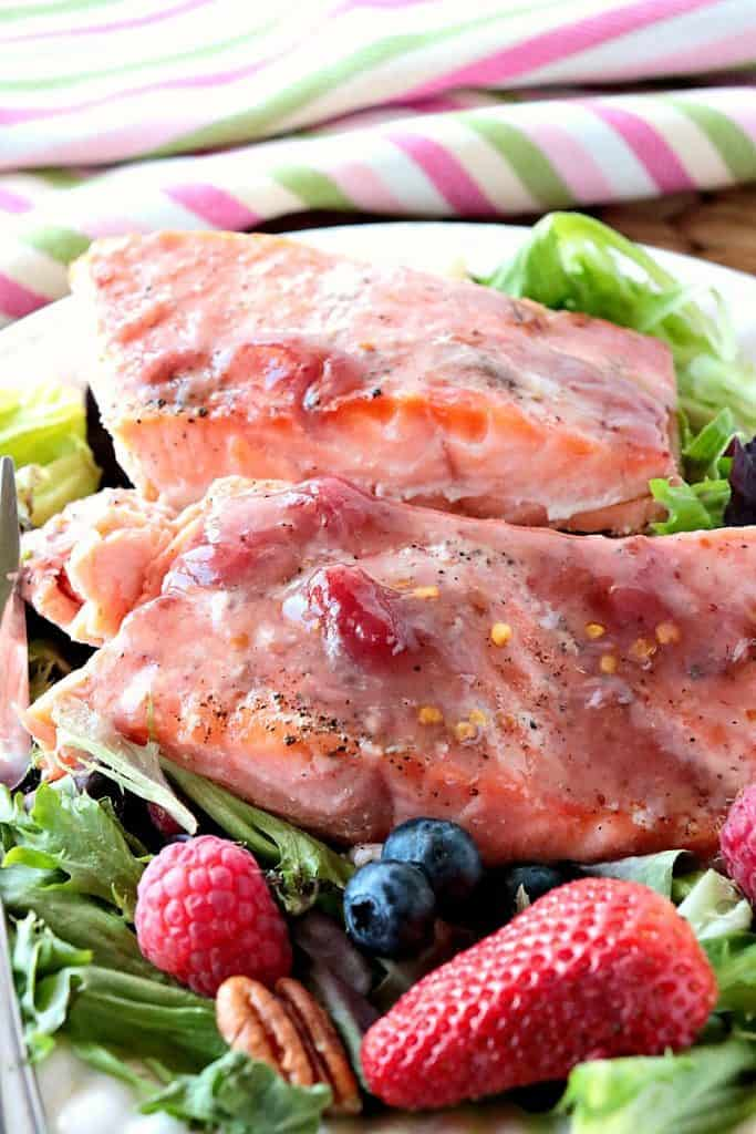 Closeup vertical picture of cooked salmon fillets with a strawberry glaze.
