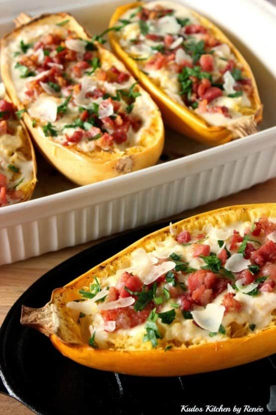 Four spaghetti squash halves filled with pancetta and Alfredo sauce with basil.