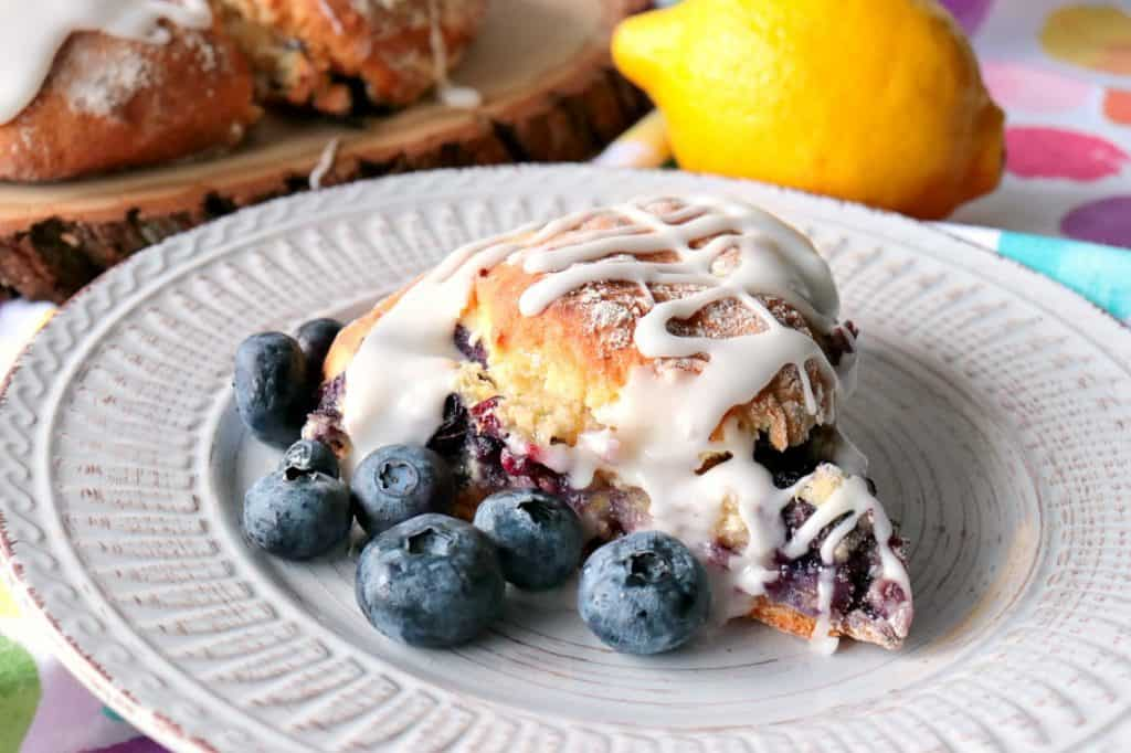 Scone on a plate with fresh blueberries, thick icing, and a lemon in the background