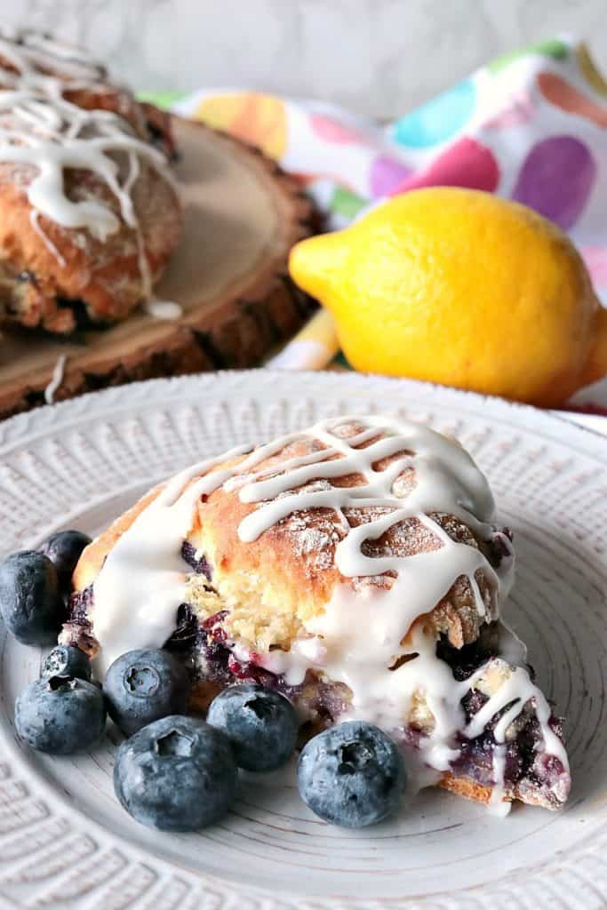 Vertical image of a fresh blueberry scone in the foreground and a muti-color polka dot napkin in the background with a lemon.