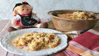 A German Spaetzle Casserole in a round tan dish with a little German doll in the background.