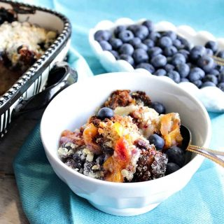 A horizontal photo of a dish of Blueberry Peach Crisp in the foreground along with a bowl of fresh blueberries in the background.