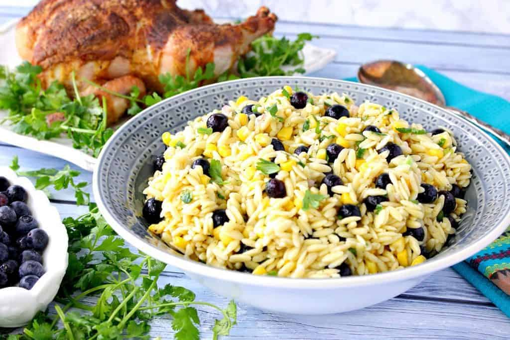 A blue bowl filled with Chilled Orzo Pasta Salad with Corn and Blueberry