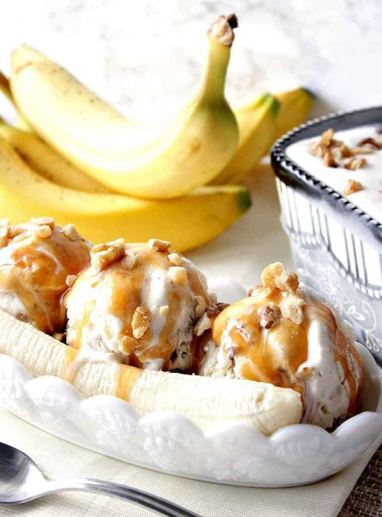 Vertical closeup photo of a dish of banana walnut ice cream with bananas in the background and carmel sauce on top.