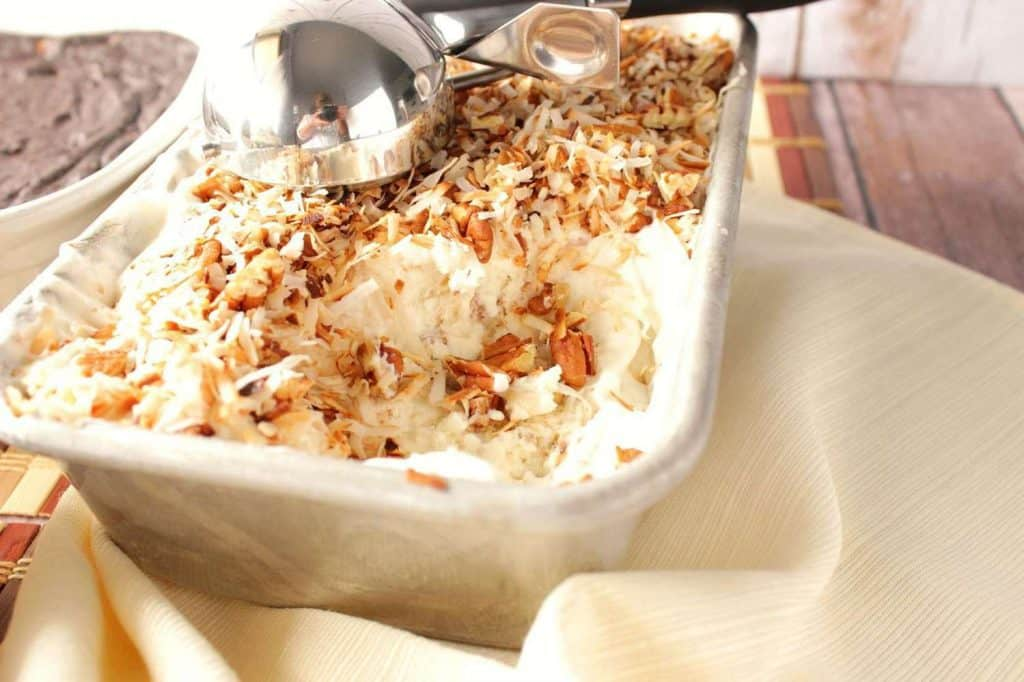 A loaf pan filled with Toasted Coconut Pecan No-Churn Ice Cream with an ice cream scoop included.