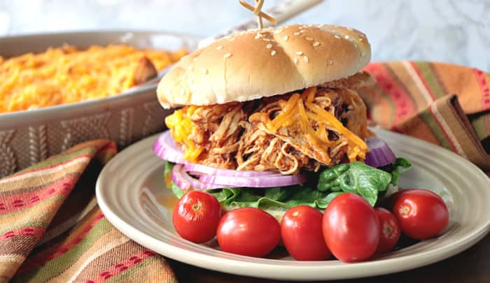 A shredded salsa chicken sandwich on a plate with tomatoes and a dish of salsa chicken in the background.