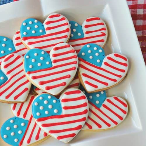 A horizontal photo of American Flag Heart decorated cookies on a square white plate with a red and white checked napkin underneath.