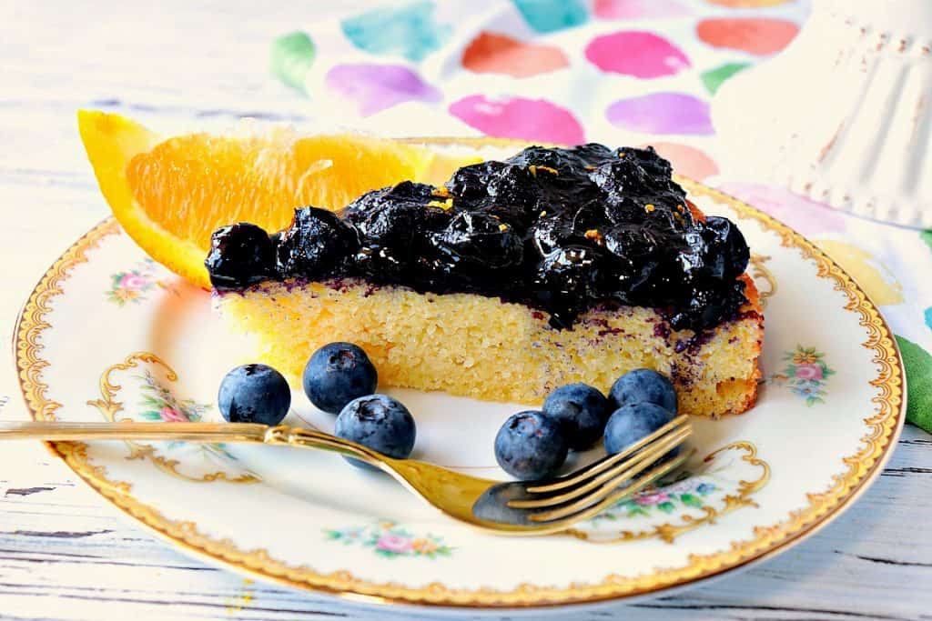 Slice of almond cake on a china plate with fresh blueberries and an orange slice.