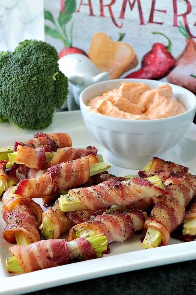 Closeup vertical photo of bacon wrapped broccoli stalks with dipping sauce. New Year's eve appetizers and drinks recipe roundup.