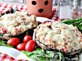 Two Chicken Parmesan Stuffed Portobellos on a plate with lettuce and tomatoes.