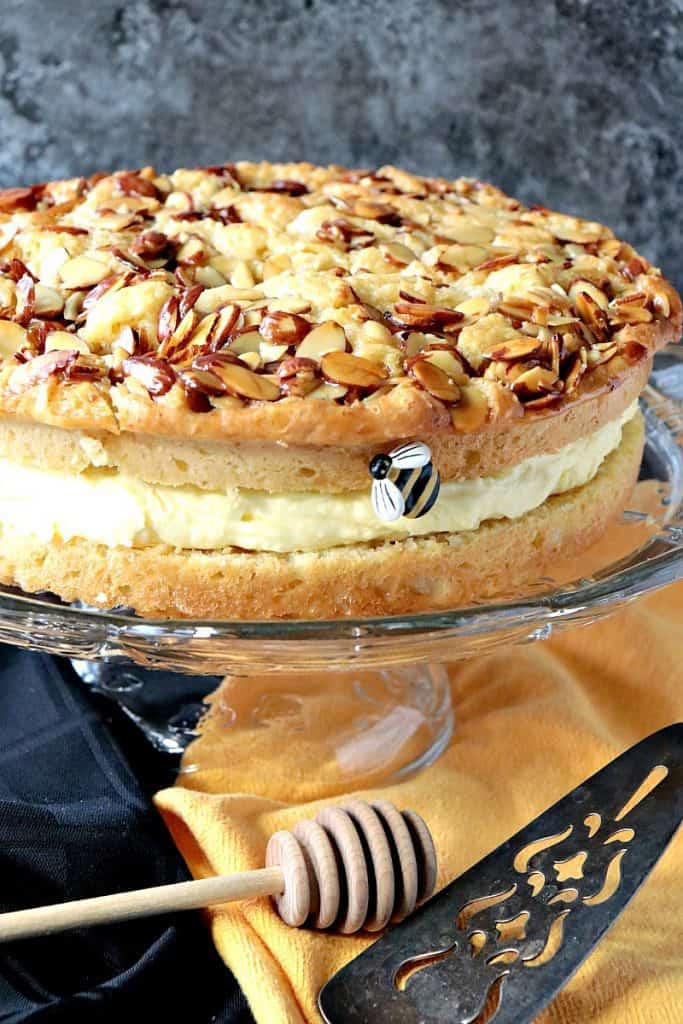 Vertical closeup image of a German bee sting cake with honeyed almonds and a cream filling on a glass cake stand.