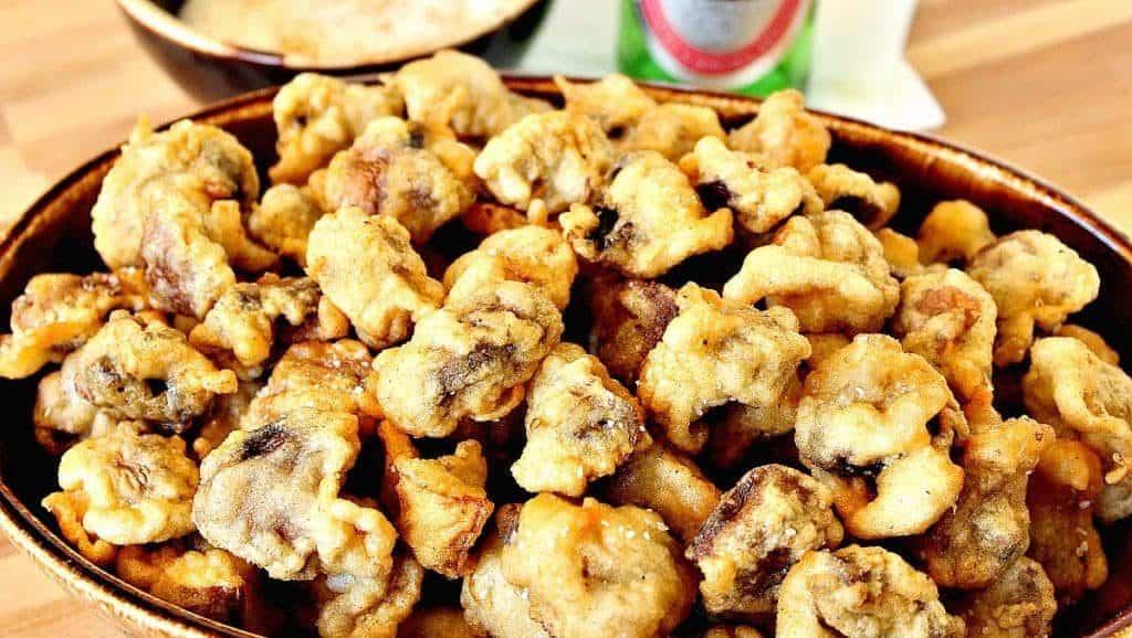Closeup photo of a large bowl of fried mushrooms.