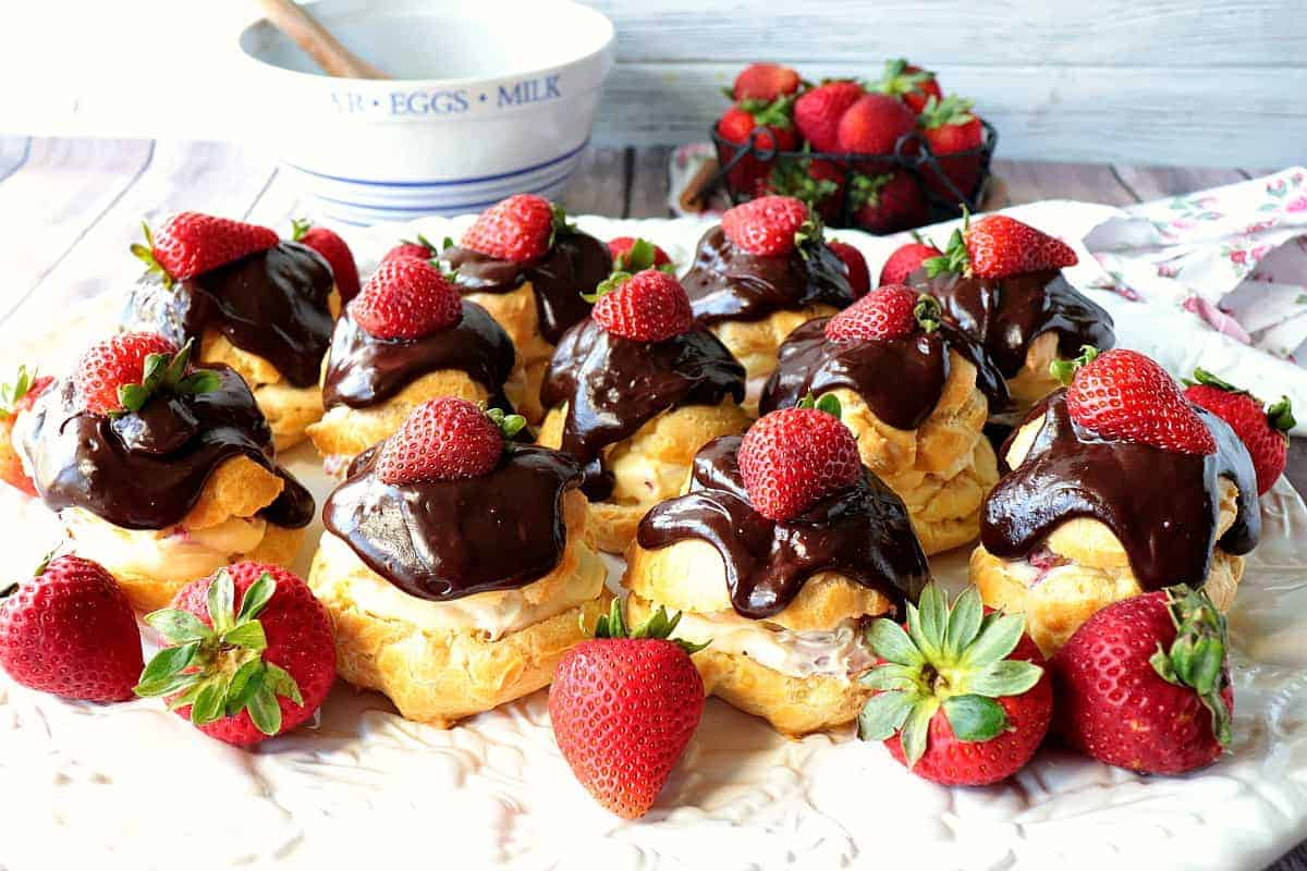 A pretty horizontal photo of a platter of chocolate covered eclairs with strawberries. Elegant chocolate dessert recipes for Valentine's day.