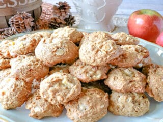 A platter filled with Apple Oatmeal Cookies with a basket in the background and some fresh apples.