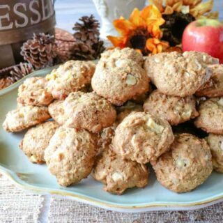 A platter of apple oatmeal cookies with fresh apples in the background and sunflowers
