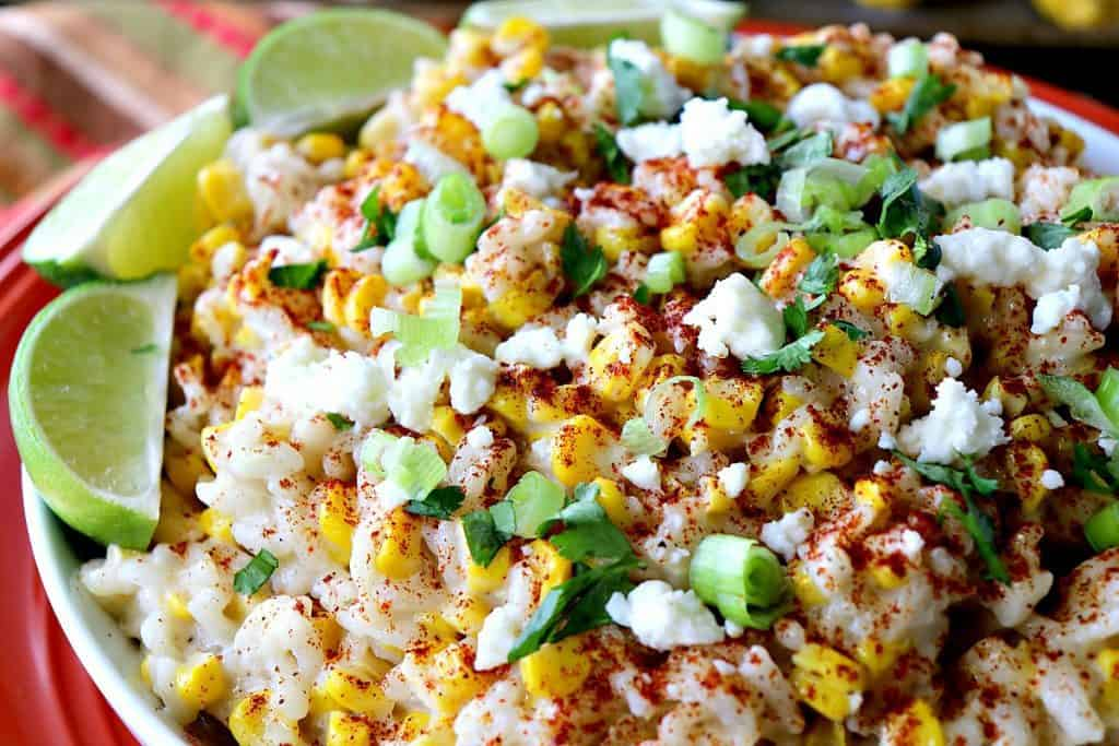 A closeup of a bowlful of Mexican street corn risotto with cheese, green onion, and lime wedges.