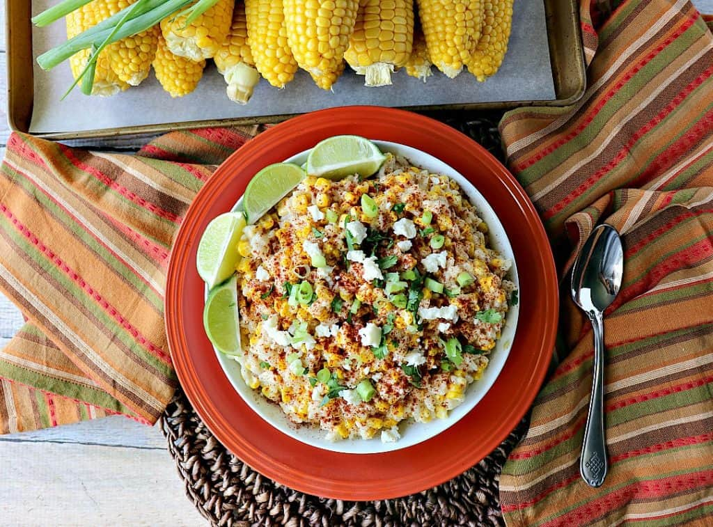 Overhead photo of a bowl of Mexican street corn risotto with a spoon and a tray of corn on the cob.