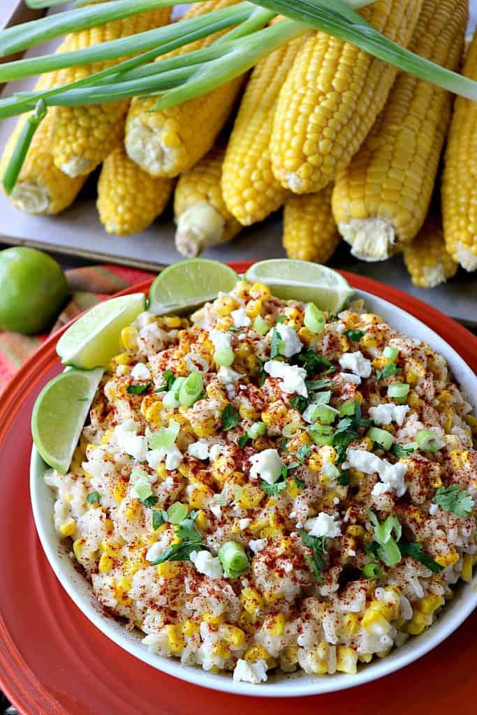 A colorful bowl of Mexican street corn risotto with limes, cheese, scallions and corn on the cob.