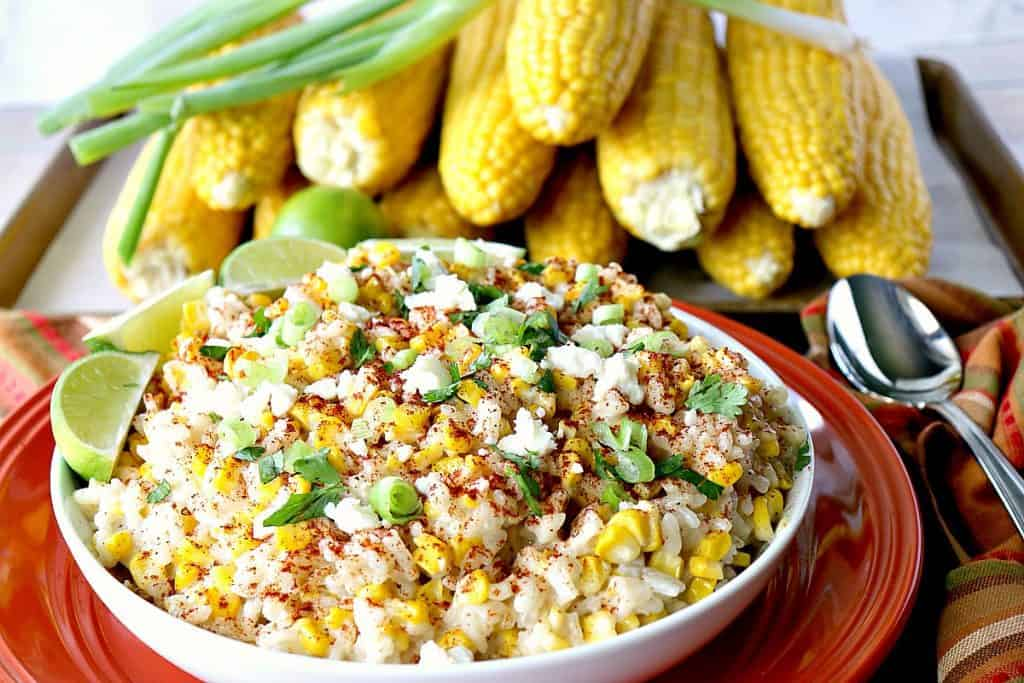 Sweet & Savory Roasted Mexican Sweet Corn Risotto with lime wedges, scallions and corn on the cob in the background.