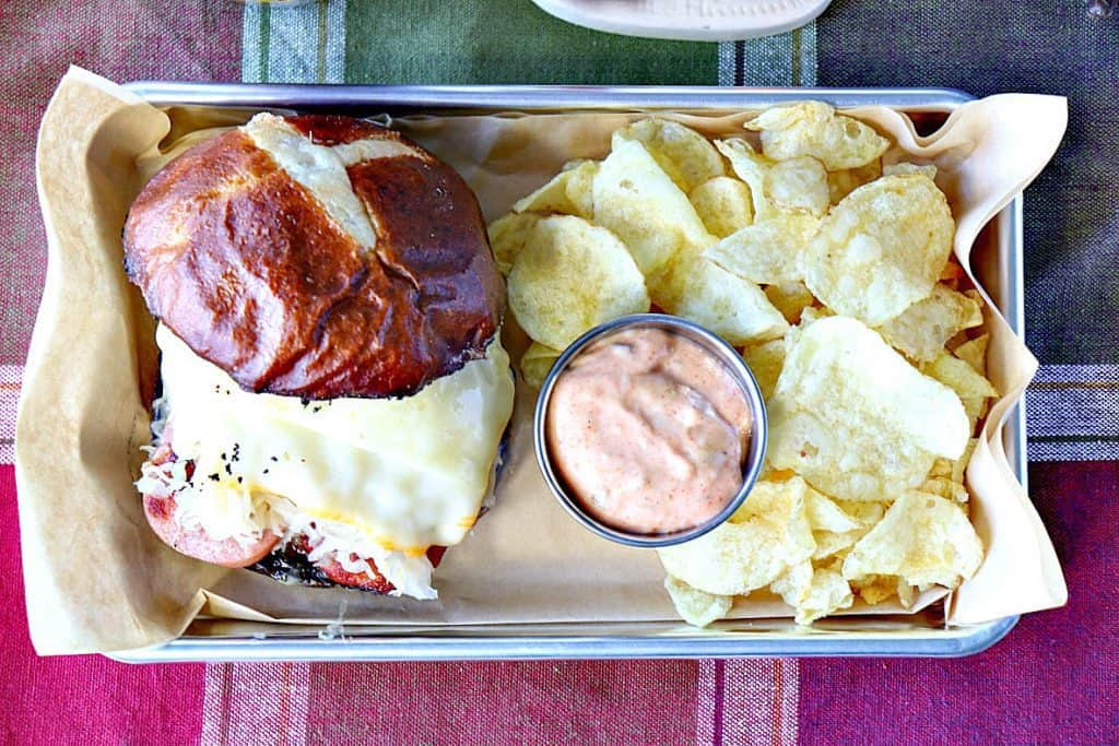 Overhead photo of a knockwurst sausage recipe on a pretzel roll with melted cheese, sauerkraut, chips, and sauce.