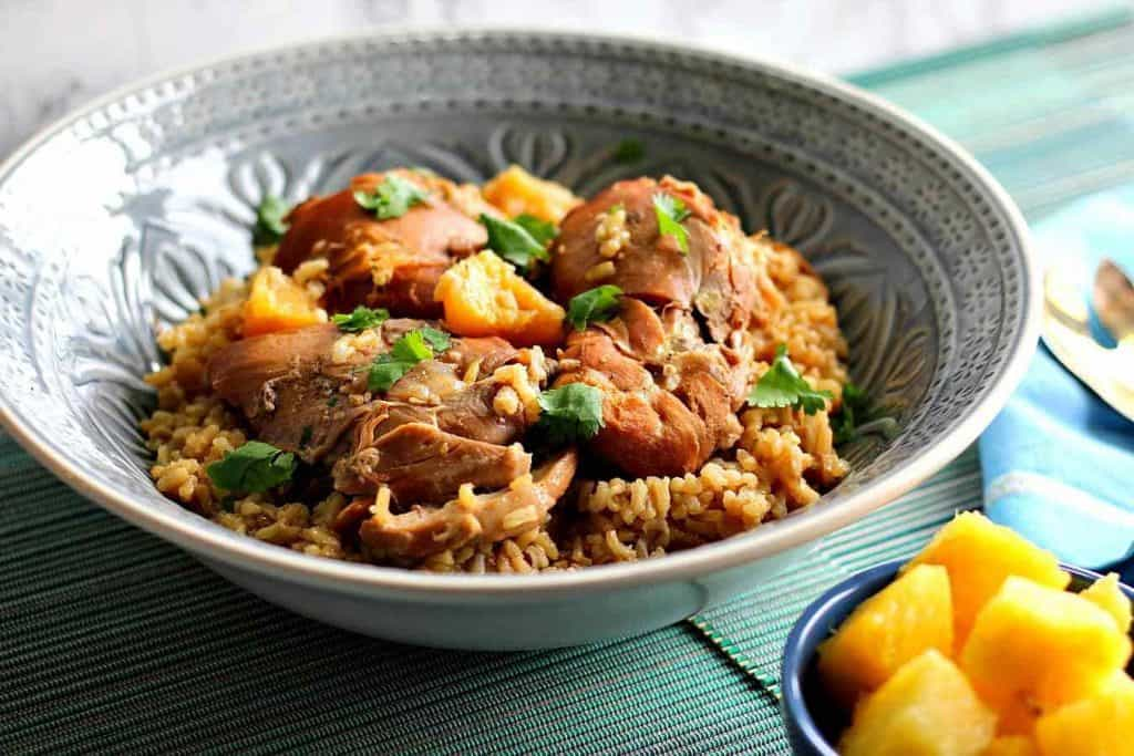 Slow Cooker Hawaiian Pineapple chicken thighs in a blue bowl over rice