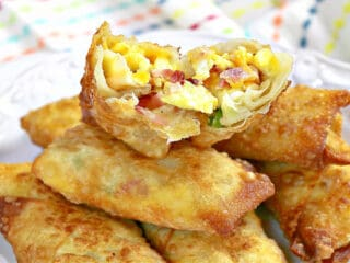 A stack of Scrambled Eggs Rolls on a white plate.