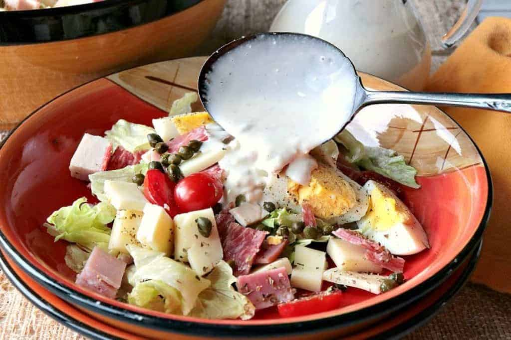 Easy Weeknight Dinner Recipes. Chef's salad in a bowl with blue cheese dressing being added.