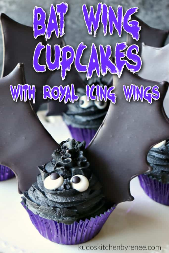A vertical closeup image of a bat wing cupcake with royal icing wings and a title text overlay graphic in purple and white