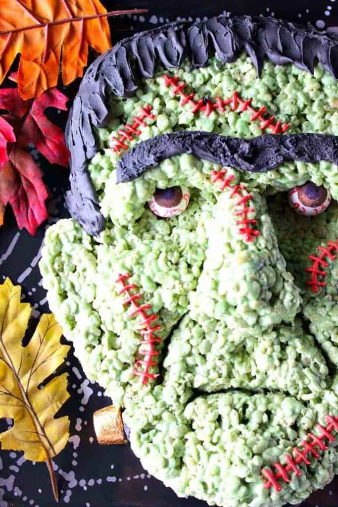 Closeup overhead photo of a Frankenstein rice cereal treat with autumn leaves and gumball eyes.