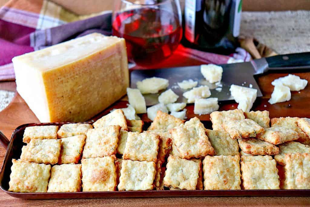 A horizontal photo of a tray of Parmesan fennel crackers with a wedge of Parmesan cheese in the background.