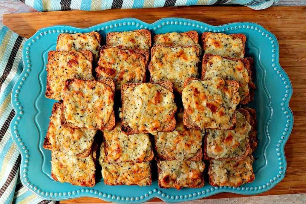 A plate full of Parmesan onion appetizer squares with a blue striped napkin.