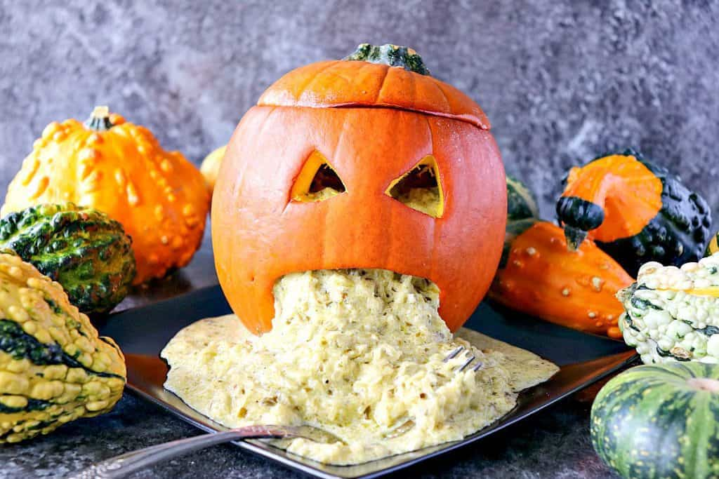 Horizontal Halloween photo of a jack-o-lantern on a black plate with squash and vomit.