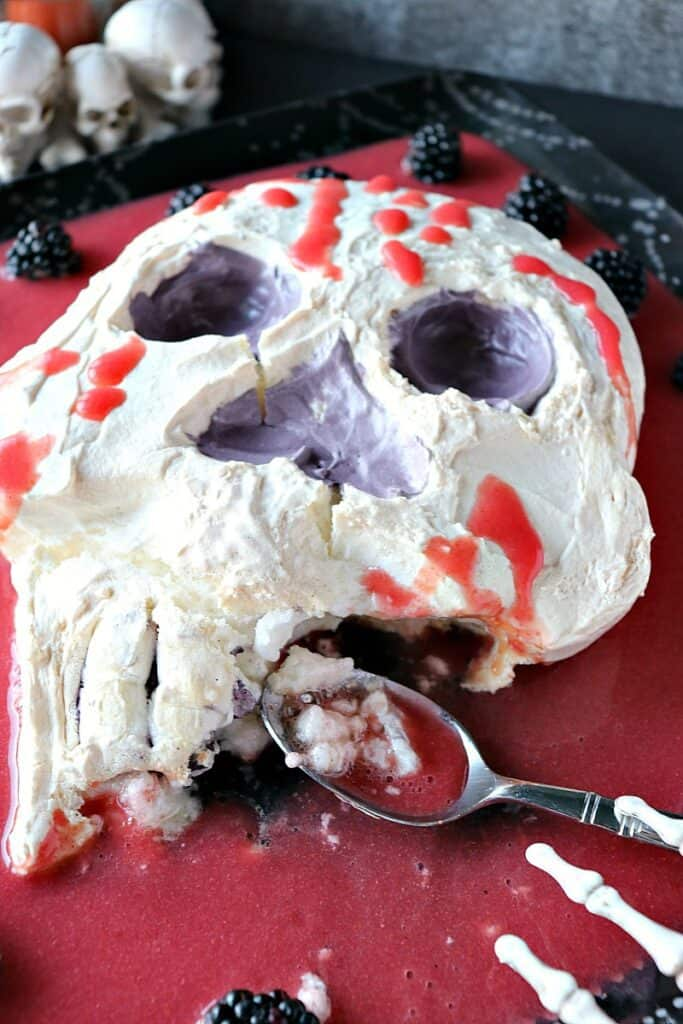 """A vertical photo of a Swiss Meringue Skull with strawberry """"blood"""" that's been partially eaten."""